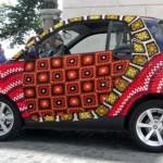 Um carro compacto Smart coberto por pontos de crochê