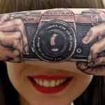 Ilusão de ótica de câmera fotográfica tatuada no braço