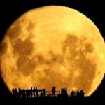 Silhuetas humanas contra a Lua Cheia em movimento
