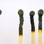 Esculturas de cabeças em palitos de fósforo queimados