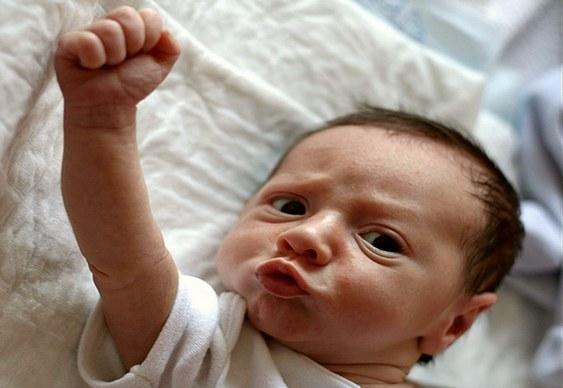 Neném com punhos cerrados