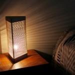 Uma luminária de cabeceira feita com madeira e elásticos