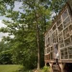 Casa nas montanhas com a fachada toda de janelas de vidro