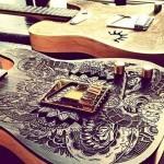 Guitarras com desenhos de tatuagem gravados na madeira