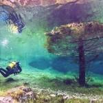 Mergulho num incrível lago verde com paisagem terrestre no fundo