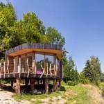 Uma casa de campo rústica de madeira queimada sobre troncos