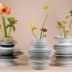 Vasos para flores com vários pratos de porcelana empilhados