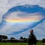 Arco-íris colorido se forma num estranho buraco de nuvem