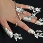 Anéis de prata com ramos de plantas brotando entre os dedos