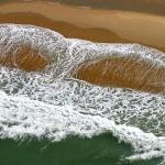 Baleia mergulha na praia em imagem criada por espuma de onda