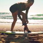 Surfista se equilibra na prancha em cima do salto alto