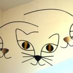 Móbiles com faces felinas e um gato descansando na prateleira
