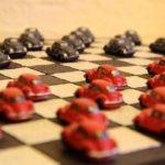 Miniaturas de fusquinhas usadas como peças no jogo de damas