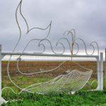 Baleia desenhada com varetas de metal em portão no litoral