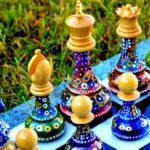 Pintura colorida revitaliza as peças velhas do jogo de xadrez