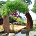 Passarela sinuosa de jardim termina em cascata de vergalhões