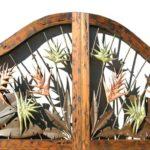 Folhagem tropical de metal em portão com moldura de madeira