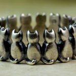 Anel ou pulseira com uma fileira de gatinhos sentados lado a lado
