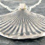 Pingente de prata com a forma de concha marinha fossilizada