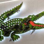 Letreiro 3D com plantas forma o crocodilo da logo Lacoste