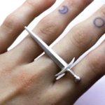 Anel místico de espada medieval paira sobre os dedos da mão