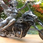 Escultura de mulher alada numa moto Harley-Davidson custom