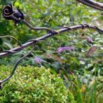 Flores e folhas de ferro em corrimão para escada num jardim