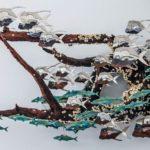 Cardume de peixes em painel de metal decora casa de praia