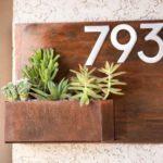Placas de metal para números de endereço com vasos de plantas