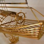 Miniatura de barco a vela feita com telas finas e varetas de metal