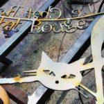 Letreiro dupla-face de ferro forjado com gato e letras vazadas