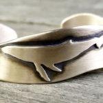 Baleia jubarte em alto-relevo num bracelete de bordas onduladas