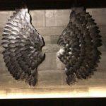 Asas de anjo em tom grafite metalizado sobre parede rústica