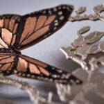 Marcador de livros com borboletas voando entre flores