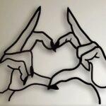Gesto de coração com as mãos em painel ou escultura de metal