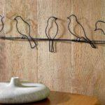 Painel com cinco passarinhos empoleirados em varetas de metal