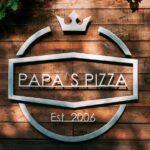 Letreiro de metal para pizzaria sobre parede de madeira rústica