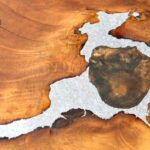 Buraco em tampo de mesa restaurado com metal fundido
