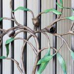 Galho de árvore em ferro forjado ornamenta porta com grade