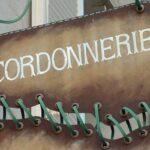 Letreiro artístico em fachada retrô de loja de conserto de sapatos