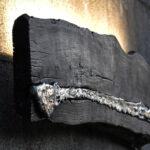 Luminária de parede feita com tábua queimada e metal reciclado