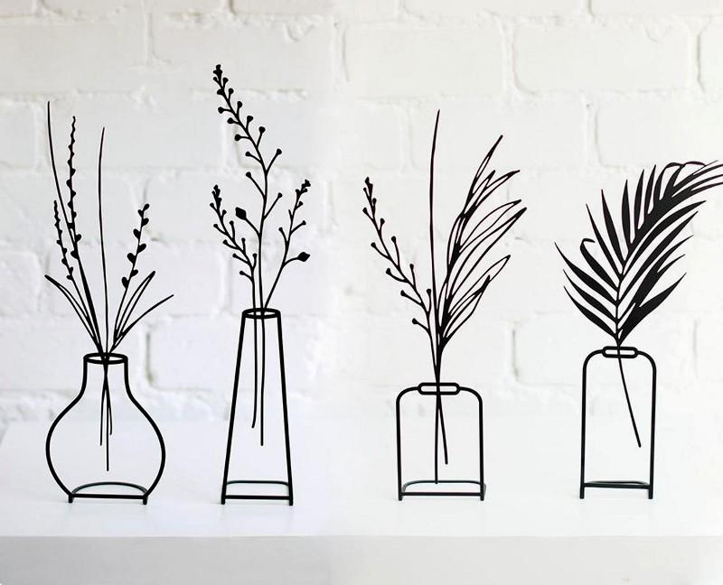Vasos com plantas em esculturas minimalistas de ferro forjado