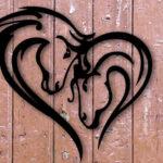 Painel de metal com duas cabeças de cavalos formando coração