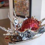 Morango caindo na colher cheia de creme em escultura de metal